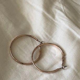 """Örhängen i form av en """"platt"""" ring. Det finns lite repor på dem men det är inget som syns på håll (alltså bara på mycket nära håll). Jag har använt de ett fåtal gånger. De är sätta att sätta i. Ingen fraktkostnad!"""