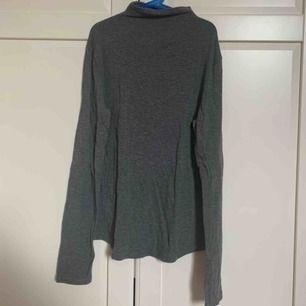 En mörkgrå långärmad tröja som har en liten krage. Ärmarna är som du ser längre än vanliga långärmade tröjor. Tröjan är även stretchig.