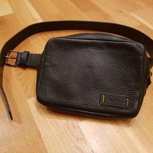 Svart skinnväska från Calvin Klein med två fack inut. Helt oanvänd. 18x13x3cm
