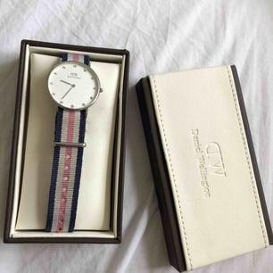 Jättefin klocka ifrån Daniel Wellington med silvriga stenar i uret och blått/rosa band! Sparsamt använd och du får med båda boxarna som är väldigt fina de också😊😊