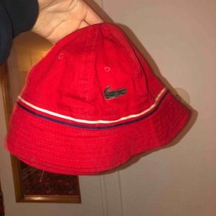 Säljer en jättefin röd solhat som är Lacoste!!🥰