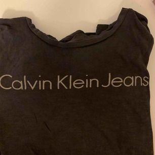En Calvin Klein tshirt som jag inte längre använder. Grå tshirt med ett grått tryck. (Samma modell som bilden med tjejen, men inte samma färg)