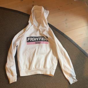 """Vit hoodie med trycket """"fighter"""" på."""