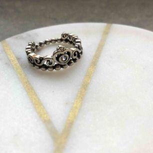 Ring formad som en krona 👑 Otroligt lik 'Pandora Tiara Ring' men tror tyvärr inte den är äkta, därav priset💛  Ringen är mörkt silverfärgad med en liten vit sten i mitten, superfin! Diametern uppmätt till 1,8cm.   Endast använd enstaka gång. Frakt 11kr⭐️
