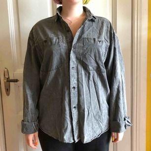 En gråspräcklig skjorta i strl m. Har en smiley på baksidan. Använd enstaka gånger. Frakt tillkommer