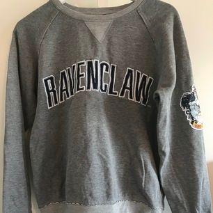 Grå tjocktröja med rawnclaw motiv och emblem. Köptes på The wizarding would of Harry Potter så officiell Harry Potter merch. Frakt betalas av köparen och ligger på ca 50 kr.