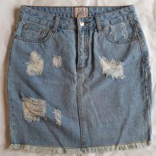 Skitsnygg jeanskjol med slitningar. Använd en gång, blev sedan för liten och har legat gömd i garderoben. Perfekt skick. Köpt på Carlings för ca 5 år sedan. Fickor både fram och bak. Frakt inräknad i priset!