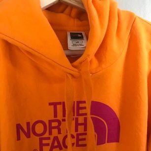 Orange hoodie med rosa tryck från The North Face. Storlek L men massage S-L. Mycket bra skick. Frakt ingår ej.