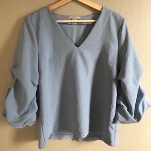 Ljusblå blus med puffärmar från H&M. Strl 36. Frakt ingår ej i priset.