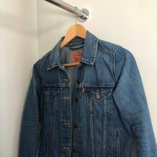 Jättefin blå jeansjacka i bra skick från Levis! Typ helt oanvänd och bra kvalitet. Säljer absolut enbart pga för liten:(( Storlek S. Frakt tillkommer