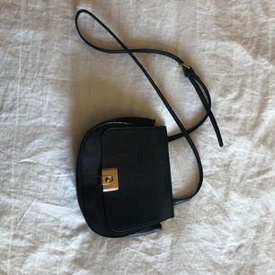 Skitsnygg svart axelremsväska i fakeskinn med gulddetaljer✨ Jättebra skick(ser ut som ny).