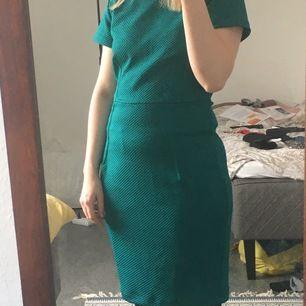Klänning som passar utmärkt som outfit till t.ex ett bröllop. Bekväm och formar kroppen fint. Har som ett rutigt mönster i en och samma grönblåa färg. Silvrig dragkedja på ryggen.