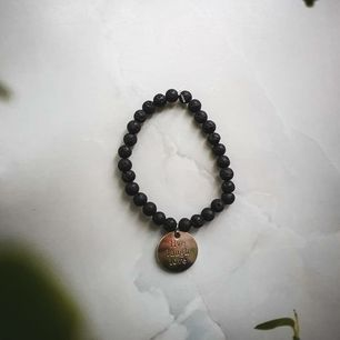 Jätte fint pärlarmband med svarta lavapärlor och silver hänge med texten
