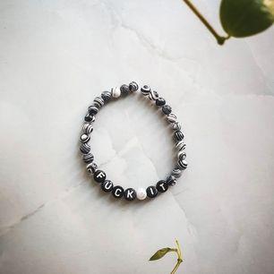 Super snyggt pärlarmband i svart och vita pärlor, med texten