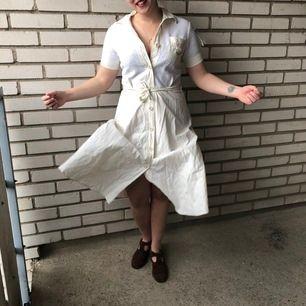 En äkta vintageklänning troligen 70-tal, i 40/50/70-talsretetrostril. Enligt ettikett strl 42, men midjemått är ca 73-75cm och bysten är snarare strl 36 (vilket också talar för äkta vintage). 90% bomull, med stickat liv och stumt bomullstyg i kjolen.