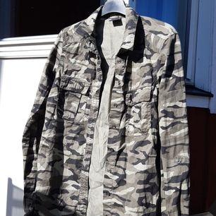 Detta är en militärskjorta i lite grön, svart och grå. Den är nästan inte använd och är varken nopprig, har hål eller är fläckig. Kontakta mig för fler bilder eller frågor och storlekar eller mått.