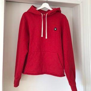 Röd hoodie från märket WoodWood, Double A collection. Är köpt i andra hand men ska aldrig ha varit använd. Har själv endast använt den en gång så mycket bra skick!
