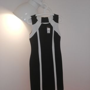New Knee-length black dress with geometric white cream line details. Falls just under the knee. Workwear.