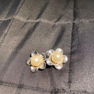 Blomm-örhängen (silverfärgat) med vit pärla i mitten från Åhléns egna märke! Nypris:120kr säljs för 52kr inklusive frakten.