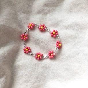 Ett pärlarmband med rosa blommor. Bra kvalitet och töjbar tråd. 11 kr frakt. (Finns också i halsband) 11 kr frakt.💖💖