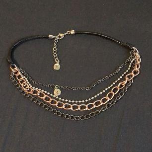 Ett halsband med fyra olika kedjor som sitter i ett läderband. Köpare står för frakt!