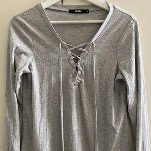 Grå, ribbad långärmad tröja med snörning framtill. Fint skick, storlek M! Köparen betalar för frakt :)