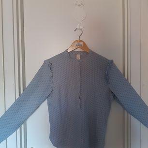 Ljusblå skjorta från H&M med svarta prickar och volanger på axlarna. Köpt 2018 och använd ett fåtal gånger efter det. Jag säljer den endast för att den är för liten för mig. Storlek 34/XS