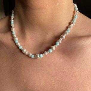 Egengjort pärlhalsband av vita, vaxade glaspärlor i olika storlekar, och blå akrylpärlor🥰 Går att förlänga med en kedja (se sista bilden), och frakt INGÅR i priset✨