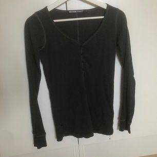 Tajt mörkgrå långärmad tröja från DrDenim. Har knappar i fram vilket ger den stilrena tröjan en lite sötare look. Storleken är XS men skulle deffenitivt passa en S/M också. Köparen står för frakten ☺️