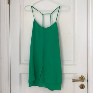 Kort klänning alternativt linne med snygg snörning. Jättefin grön färg. Frakt på 63 kr tillkommer