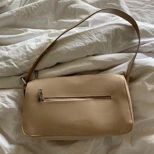 En beige väska i lack från H&M som aldrig har kommit till användning. Frakten är inräknat i priset