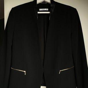 Svart blazer med skin imitation på kragen och guld detaljer. Knappt använd, köparen står för frakten. Kan ta swish!