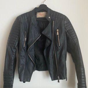 Mc-inspirerad jacka i läderimitation med quiltade detaljer på axlar och i ärmslut. Två fickor med dragkedja framtill. Reglerbara bälten på sidorna. Nypris 699kr   mitt pris 200kr