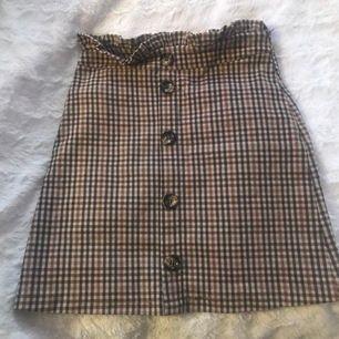 Jättesöt beige rutig kjol med knappar framtill. Den sister tajt och passar XS-S.