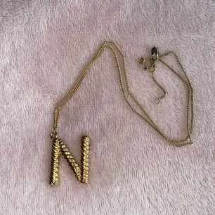 """Guldigt halsband med ett """"N"""". Använd fåtal gånger.  Köparen står för frakt."""