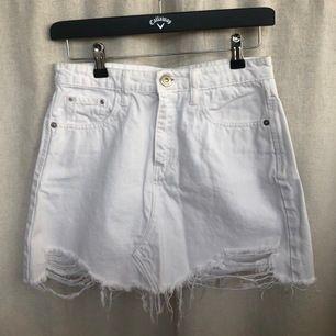 En vit jeanskjol med slitningar från river island i storlek 32, men skulle säga att den sitter mer som en 34 då den är för stor för mig. (Frakt inkluderat i priset.)