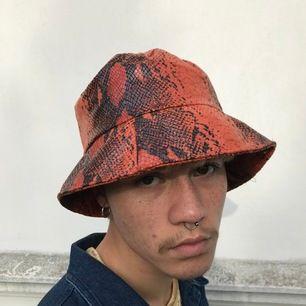 Orange/svart buckethat i ormskinn (fejk) köpt secondhand. Supercool och vill se den användas mer så säljer den! Ingen synlig slitage så är som ny.