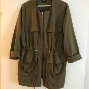 En militärgrön jacka från Monki. Snygga detaljer som dragsko i midjan. Sitter väldigt fint på. Perfekt vår/sommar och höstjacka. Fraktkostnad 88kr Postnord