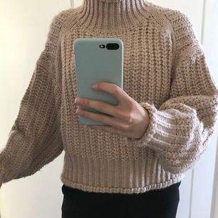 Stickad tröja från H&M i en ljusrosa färg. Tröjan har ballongärmar och hög krage. Använd ca 3 gånger, så är i mycket bra skick!