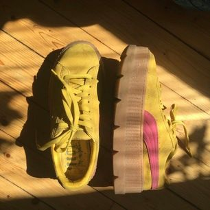 FENTY x Puma skor med platåsula. I gult med rosa märken på sidorna.