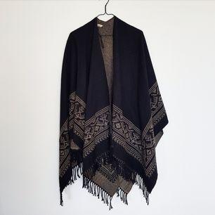 Svart poncho med brunt mönster från Åhléns i one size. Köpt 2014 för 300 kr och säljs nu för 150 kr. Kan mötas upp i Stockholm eller skicka men köparen betalar frakt!🌻