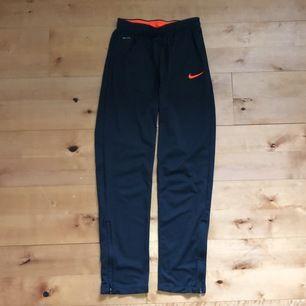 Mörkgrå/orangea träningsbyxor från Nike i mycket bra skick. Använda 4, 5 gånger. Nypris: 349 kr, nuvarande pris: 100 kr. Köparn står för frakt.