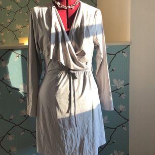 En väldigt tunn grå kappa i mockaimitation från Nly trend. Kappan har ett smalt knytband i midjan. Den kan också användas som klänning. Den når halvvägs ner på låren på mig som är 172 cm. Frakt tillkommer.