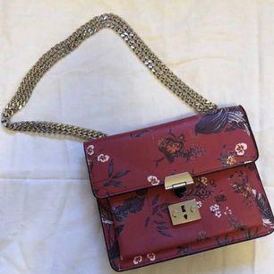 Röd väska från MANGO med blommönster och silverdetaljer. Säljer då jag knappt fått användning för den, fint skick!
