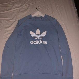 En ljusblå college tröja köpt på en adidas affär. Inga fläckar eller hål. Säljs för att den inte kommer till användning.