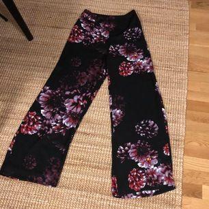 Härliga vida byxor i svart med röda/lila blommor. Höga i midjan och luftigt material😍 Från Lindex och aldrig använda. Strl 36. Mottagaren betalar frakten😊