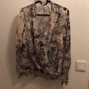 En grå/vit blus från H&M med omlott och rynk nedtill. Fin passform😍👌🏼 Lite längre baktill.