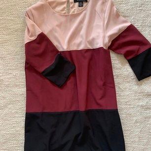 Långärmad klänning/tunika i ljusrosa, vinröd och svart. Fin, lös passform. Använd en julafton.