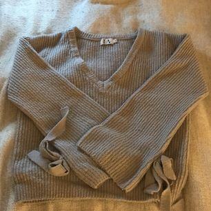 Fin stickad tröja från NA-KD! Säljer den pga för stor för mig! Det är utsvängda armar med knytningar. Den är V ringad!