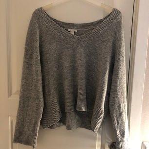 En grå stickad tröja som är lite som en shoulder tröja